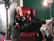 Blonde Slut In Naughty Black Latex Outfit And High Heels Sitting