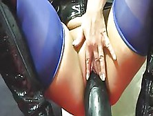 Sexy Woman In Latex Corset And Boots With High Heels Is Riding A Huge Dildo
